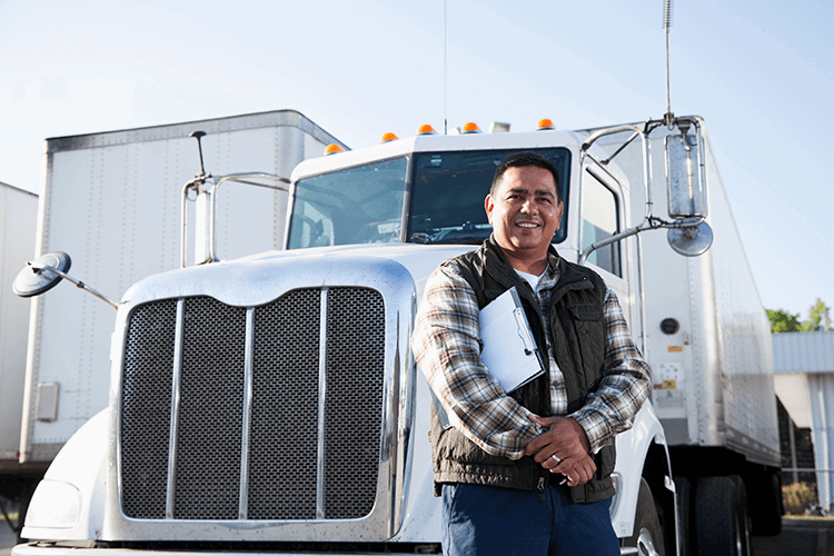 Hispanic truck driver stands beside his rig