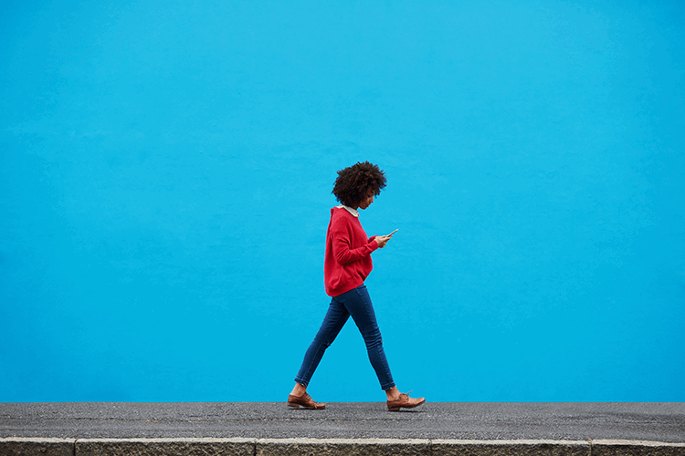 Woman walking alone looking at her phone